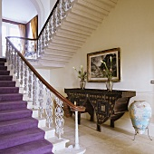 An elegant flight of stairs with a wrought iron banister and an antique washstand underneath