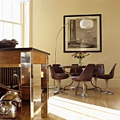 Light playing on the floor in front of a dining area with bucket chairs and a curved floor lamp