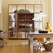 A kitchen counter with a tailor-made cupboard with square, stainless steel doors in the background