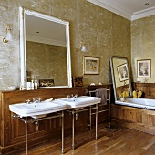 An antique bathroom with two wash basins and a mirror hung on a gold-painted wall above wood panelling