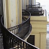 A curved balcony railing on the facade of an urban villa