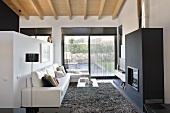 Designer-Wohnzimmer mit Gartenblick - Ledersofa vor Raumteiler gegenüber schwarzem Kaminofen
