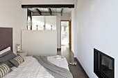 A bedroom with built-in television, a room divider and a view in a bathroom