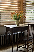 A bunch of garden flowers on a simple wooden davenport with a chair in front of wooden blinds