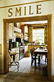 The word 'Smile' written above a doorway with a view into a country house kitchen