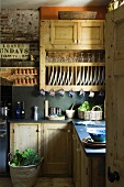 A rustic fitted kitchen with wooden cupboards and a built-in plate rack