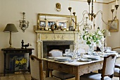 An dinner invitation - a table laid in the fireplace room of a country house with a chandelier hanging from the ceiling