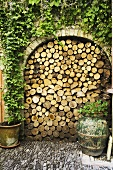 A rounded archway in a courtyard filled with firewood