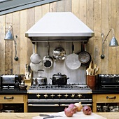 An old kitchen oven hung with pots against a wooden wall