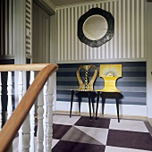 Artistically painted chairs against a striped wall in a stairway