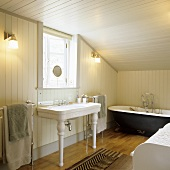 Vintage furniture in a bathroom in the attic of a country house with wood panelling