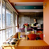 A view into an open-plan kitchen: a woman stands in the dining area with colored chairs in front of a glass facade