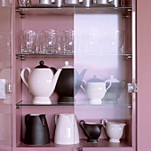 Black and white jugs, pots and glasses in a pink-painted cupboard with open glass doors