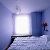 A small bedroom with a blind at the window and floor-to-ceiling wardrode