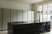 A black kitchen counter with bar stools in front of a window and a kitchen cupboard with a metal front