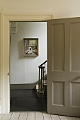 An open door with a view into a stairway with a picture on the wall