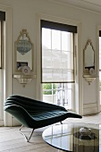 A curved chaise lounge in front of a floor-to-ceiling window with a blind and antique brackets on the walls with mirrors above them