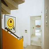 A stairway with a banister rail mounted on an orange panel and a view through an open door into the hallway