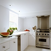 Slices of melon on a kitchen work surface and a stainless steel cooker with an extractor fan
