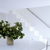 A white room with a vase on a table and a flight of stairs with a stainless steel banister rail