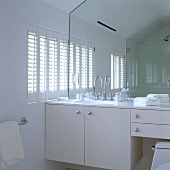 A white bathroom in an attic - a wash basin with a built-in cupboard and a full-wall mirror