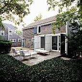 Einfamilienhaus mit offenstehenden Türläden und Terrasse mit Polstermöbel