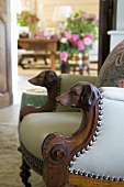 An antique leather chair with wooden arm rests carved with dog heads