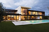 Evening atmosphere - an illuminated villa with a glass facade and a pool