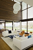 A white seating area with and designer lamp in a newly built villa with a glass facade