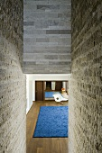 A natural stone wall with a view through a narrow opening into a living room with a wooden floor and a blue rug