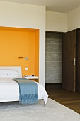 A bedroom with a bed in an orange-painted wall niche and an open door