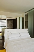A double bed with white bedclothes and a mirrored cabinet in a bedroom