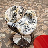 A floral pattern on an upholstered designer chair with a metal foots and a floral carpet