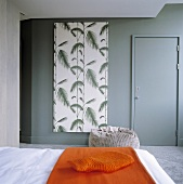 An orange quilt on a bed and a door in a grey wall