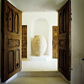 A view through open double door onto a an amphora in a wall niche in a Mediterranean house