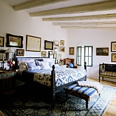 A bed with a blue and white quilt and an upholstered bench in a bedroom in Mediterranean country house with a wood beam ceiling