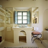 A Mediterranean bathroom - a stone washstand with an arched base and a window with blue shutters on the inside