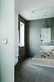 A grey tiled designer bathroom with a wash basin on a shelf