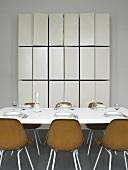 A table laid with brown bucket chairs and a tailor-made wall cupboard with open doors