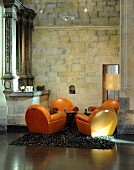 A seating area in a converted church - orange leather upholstered armchairs on a flokati rug in front of a natural stone wall