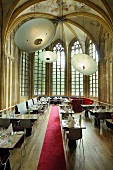 A designer restaurant in a converted church with a red carpet and extra large lampshades in the vaulted ceiling