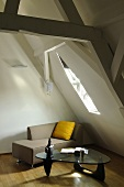 A renovated attic with a modern chaise longue under the skylight