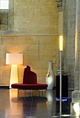 A designer seating area in a renovated church - a red circular bench and a floor lamp against a natural stone wall