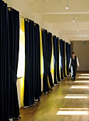 A woman in a corridor with half-closed, two-tone curtains hanging at the windows