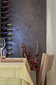 A corner in a designer restaurant - a table and chairs and a wine rack against a shiny, dark wall