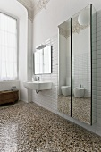 A stately bathroom with a terrazzo floor and a mirrored cupboard next to the wash basin