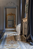 An anteroom with a view through a door onto a wall mirror with a gold frame and a patterned terrazzo floor