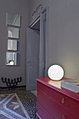 A ball-shaped lamp on a red chest of drawers and an artistic mirror installation