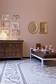 A child's bedroom - an antique chest of drawers and a collection of dolls on the bed in front of a pink wall and a patterned terrazzo floor