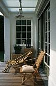 Sonniges Plätzchen auf der Loggia mit Holzliegestühlen